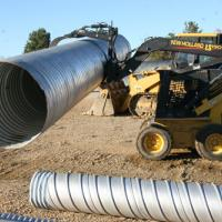 grapple carrying culvert pipe